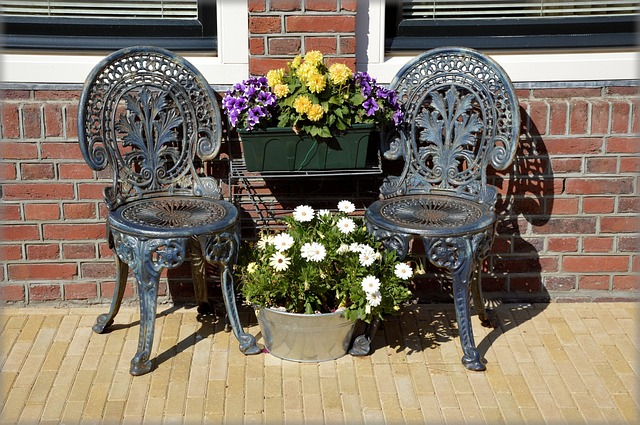 two iron chairs with flowers on patio